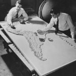 Black and white photograph of two men painting a raised relief map